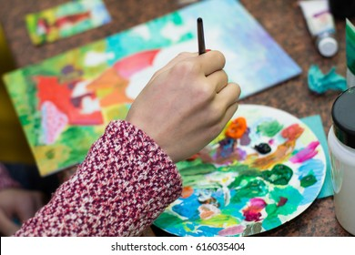 Palette with acrylic paints. Many colors. Lie brushes and palette. Drawing lesson for children and zvroslyh. Creation. Art therapy. The artist paints a picture. Brush in hand. Painting on canvas.