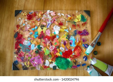 Palette of the artist with tubes of paint and brushes. Close up. Textured colorful art background.