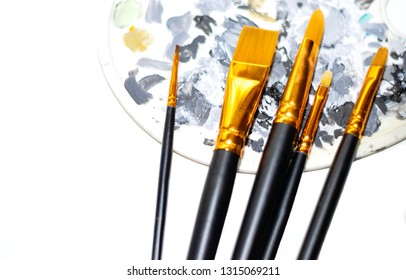 palette with color selection and artistic paint brushes for drawing on an isolated white background close-up