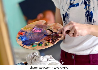 Palette with colors in the hand of the girl. cleans off unnecessary paint. The concept of fine arts