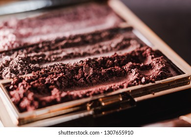 palette with crushed powder eyeshadows in nude and blush tones on dark background, concept of beauty and make-up trends