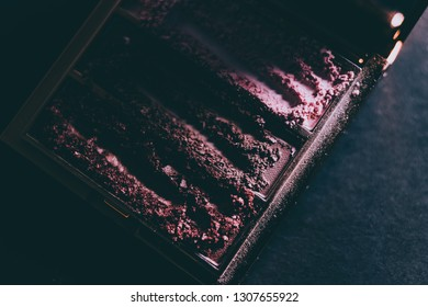 palette with crushed powder eyeshadows in nude and blush tones on dark background shot with moody lighting, concept of beauty and make-up trends