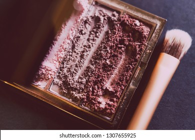 palette with crushed powder eyeshadows in nude and blush tones on dark background with brush, concept of beauty and make-up trends