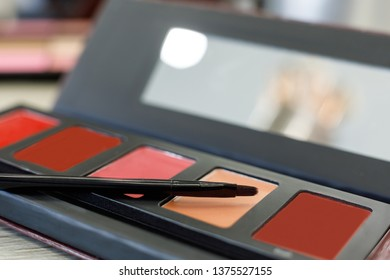 Palette with lip gloss, brush on the table in the beauty salon. - Shutterstock ID 1375527155