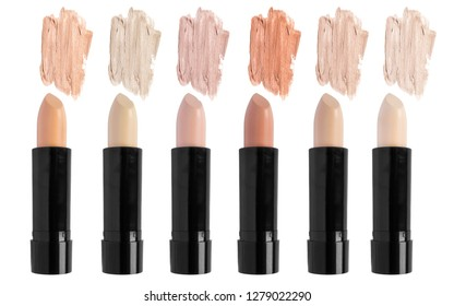 Palette of nude cream concealer sticks isolated over white