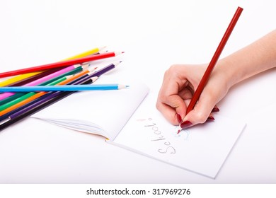 Palette set of colorful sharp pencils brown red yellow blue green violet pink purple lilac and orange colors lying near drawing human hand on paper sheet on white background, horizontal picture