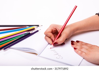Palette set of colorful sharp pencils brown red yellow blue green violet pink purple lilac and orange colors lying near drawing human hand on paper album on white background, horizontal picture
