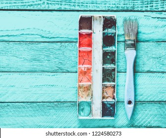 Palette of watercolor paint and a brush for painting on a turquoise wooden boards. Top view. Copy space. Art concept.