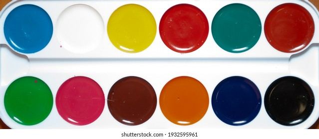 Palette of watercolor paints on a white background .