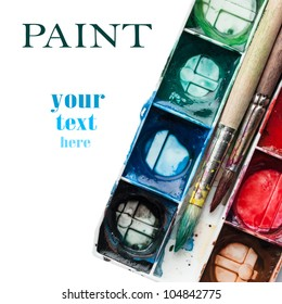 Palette of watercolor paints with paintbrushes and space for your text.