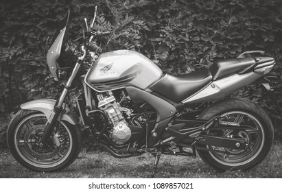 Palic, Serbia: May 13, 2018. Honda CBR 600 japan motorcycle from 2009, photographed outdoor in the park. Nice sunny day. Yellow metallic color. Comfort and sport characteristics. Black and white photo
