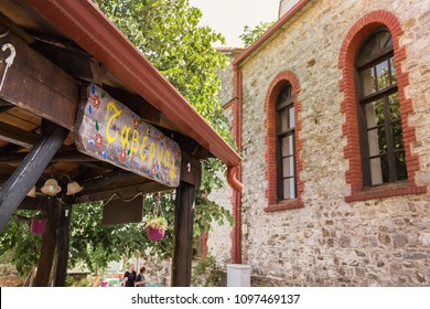 Palios Panteleimonas, Greece - May 1th, 2018: Taverna wooden board sign hand made hanging from the roof of a traditional Greek Tavern.