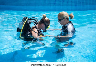 Paliouri,Greece - June 15 2016:Young woman tries a scuba dive in a pool with an instructor.Scuba diving is a sport enjoyed by many .Photographs taken in an open pool with no photography restrictions