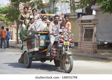 PALITANA, INDIA - MARCH 02: Unidentified travellers take a local 'Chakdas' motorcycle rickshaw on March 02, 2012  Palitana, Gujarat, India. Local transport is cheap but is often overcrowded.
