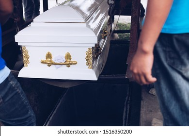 Pallbearers carefully oversee the process of lowering the casket to the ground for the deceased to its final place of rest, during the burial service or ceremony or funeral rite in the cemetery.