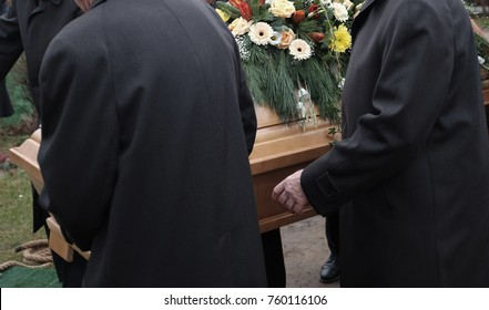 Pallbearers carry a coffin decorated with flowers