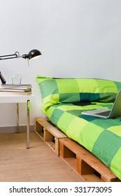 Pallet bed diy in modern bedroom with laptop