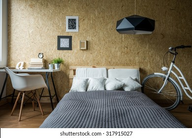 Pallet bed and wooden wall in ecological bedroom