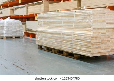 Pallet with boards in the hardware store. Packed boards in the building store. dry flat boards stacked together. building materials. warehouse with variety of timber for construction and repair.
