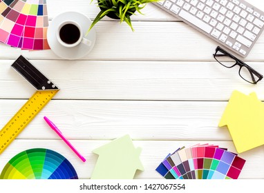 Pallet, keyboard, house, coffee and tools for architect work on white wooden desk background top view copyspace frame