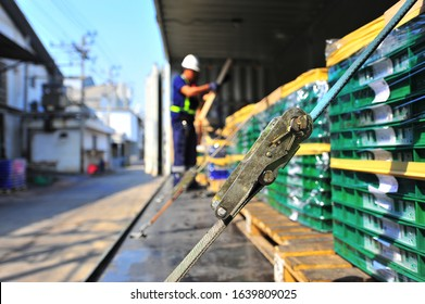 Pallets Load of green plastics container with a Film Wrapped and Strapped up with green ratchet straps on the truck.