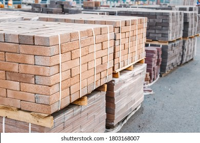 pallets and packages of freshly produced red bricks in a construction warehouse on the street. Concept of repair and building materials