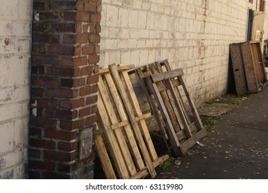 Pallets sit abandoned in an empty alleyway