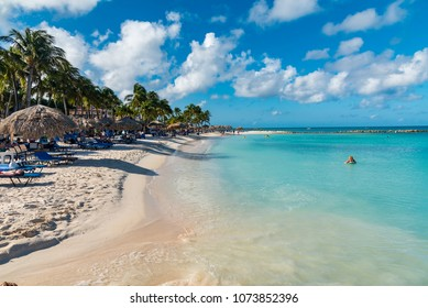 Palm Beach, Aruba - January 15 2018: long beach of fine white sand with palm trees of the large luxury hotels of the Caribbean Sea on the island of Aruba