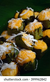Palm Cake, yellow color of Thai dessert top with shredded young coconut in the small banana leaf package: focus in the middle one
