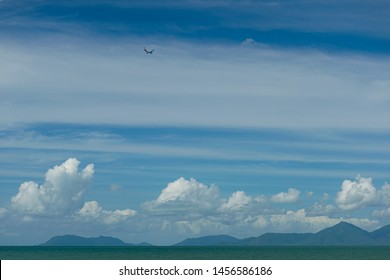Palm Cove, Queensland - May 29, 2019: Hills over green sea with white clouds and Qantas aeroplane on approach to Cairns airport