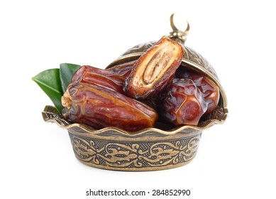Palm dates on the bronze plate, white background