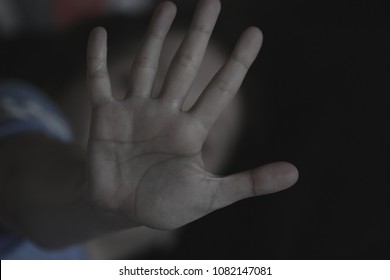 The palm of a female hand giving the signal to stop. The dark, moody image is a concept of a woman being abused, raped, beaten, threatened, robbed, domestic violence etc. A sign of the #metoo movement