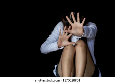 The palm of a female hand giving the signal to stop. The dark, moody image is a concept of a woman being abused, raped, beaten, threatened, robbed, domestic violence etc.