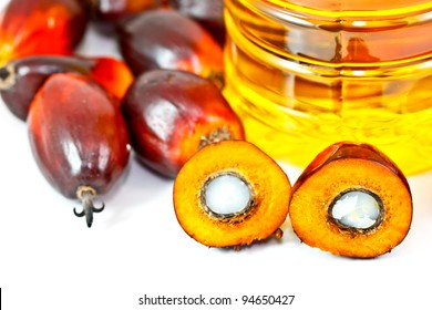 palm fruits and palm oil, one fruit is cut to show its kernel inside