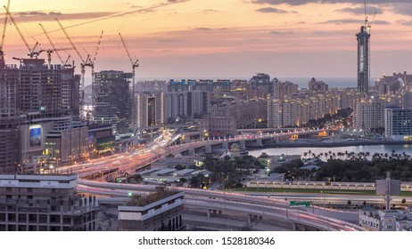 Palm Jumeirah Highway bridge aerial day to night timelapse. View from Internet city with traffic and construction site. Dubai, United Arab Emirates