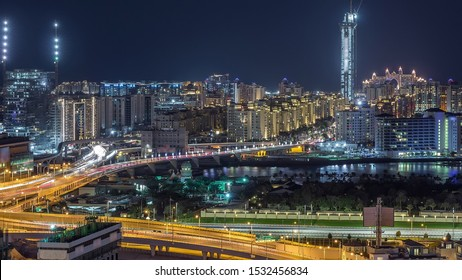 Palm Jumeirah Highway bridge aerial night timelapse. View from Internet city with traffic and construction site. Dubai, United Arab Emirates