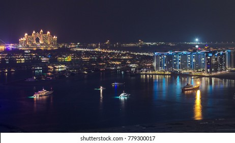 Palm Jumeirah with yahcts with hotel at night view from skyscraper Dubai marina timelapse,Palm Jumeirah is a hugely popular residential area located in the sea.