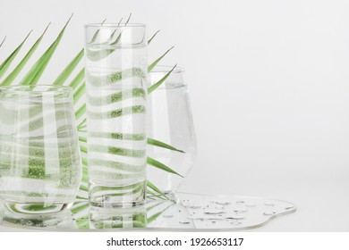 palm leaf distorted through water in glasses with mirror on white background. pure water , relax , surreal ,eco-friendly home concept. copy space.