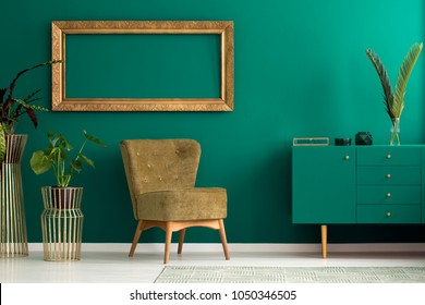 Palm leaf on a modern, teal sideboard with drawers in a luxurious, green living room interior with golden decorations and an upholstered chair