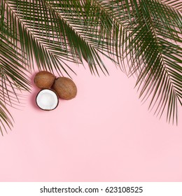 Palm leaves and coconuts whole and halves of coconut on a pink pastel background