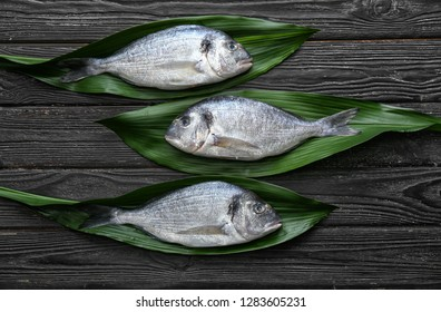 Palm leaves with fresh dorado fish on wooden background