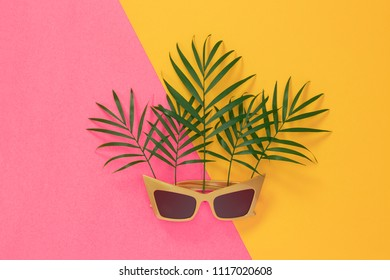 Palm leaves and sunglasses on vibrant pink and yellow background. Tropical summer theme.