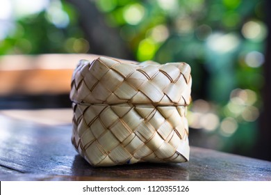 Palm leaves weaving, Thai sticky rice container, on wooden table in home kitchen or resturant, keep rice warm. Natural product, reuse and environmental friendly and safety material.