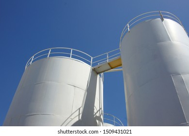 Palm oil storage tank white against blue skies