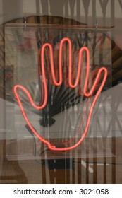 a palm reader hand design made out of neon in a window