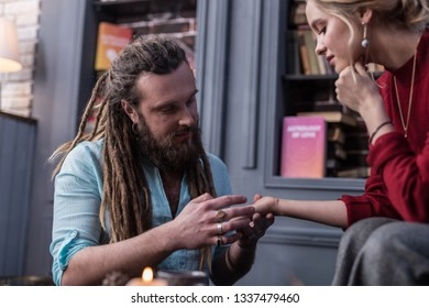 Palm reader. Positive bearded man looking at his clients hand while working as a chiromancer