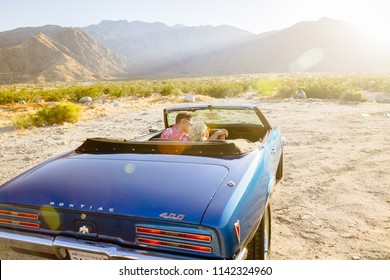 Palm Springs, CA / USA - 05/17/2017: Man and woman couple driving off into sunset in blue convertible in the desert at sunset