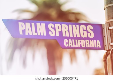 Palm Springs California Street Sign. A street sign marking Palm Springs, California. Backed by a palm tree with a sunset flare.