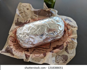 Palm Springs, California, United States - October 27, 2018: Chipotle Mexican Grill burrito wrapped in tin foil in a basket with  Tabasco sauce. With more than 1600 locations, Chipotle had a net income