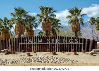 PALM SPRINGS, USA - FEBRUARY 15 2018: View of the city of Palm Springs entrance sign with palm trees growing behind it